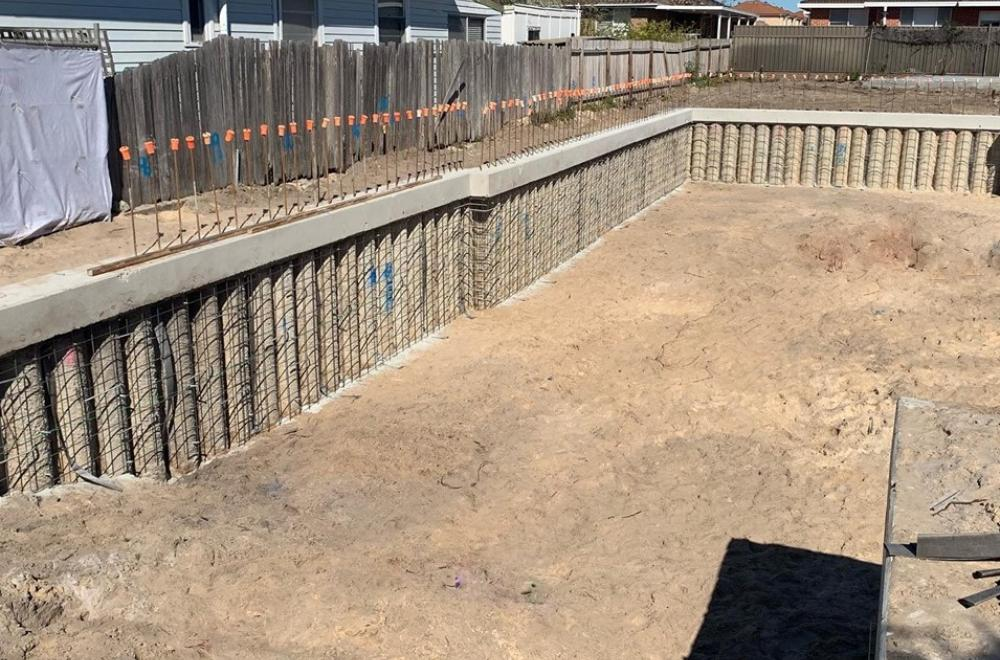 Contiguous piled wall with capping beam